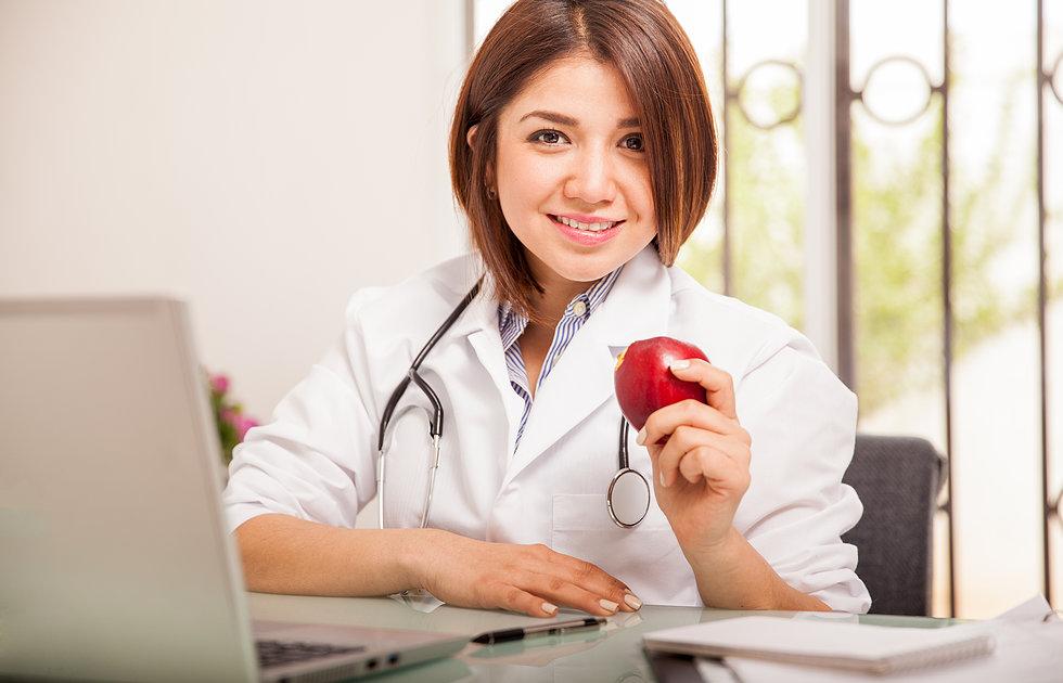 Médica sorridente com fruta na mão | 31 de março - Dia da Saúde e Nutrição