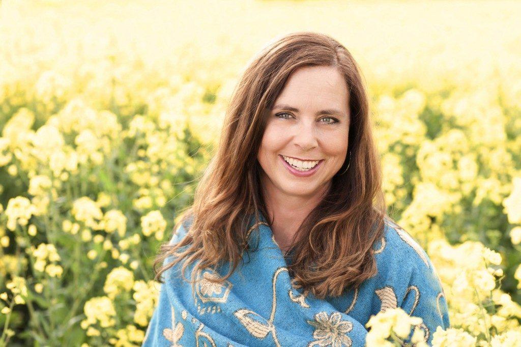 Mulher de 40 anos sorrindo em campo de flores amarelas | Como viver bem com a menopausa
